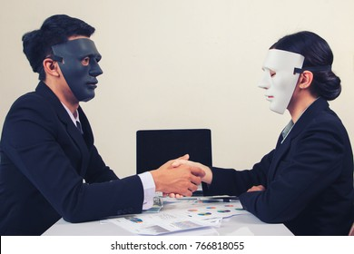 young business giving dishonest handshake hiding in the mask - Business fraud and hypocrite agreement.