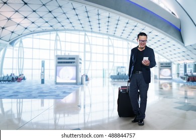 Young business man in airport.  businessman using smartphone smiling happy inside building of airport.