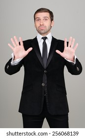 Young business man in black suit making calm down gesture. Studio portrait. Easy. Relax.