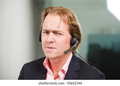 Young business man blond hair with headset wearing blue suit and pink shirt