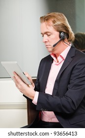Young business man blond hair with headset and tablet wearing blue suit and pink shirt in front of window.