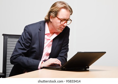 Young business man blond hair working with laptop isolated on white background. Wearing glasses blue suit and pink shirt.