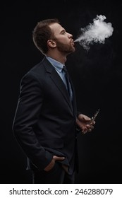 young business man blowing smoke of electronic cigarette on dark background