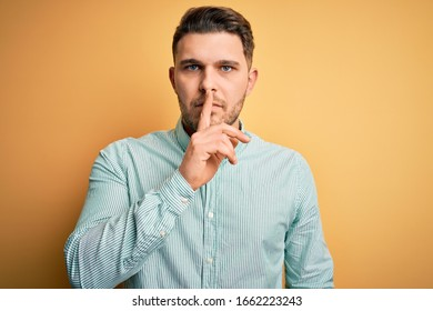Young business man with blue eyes wearing elegant green shirt over yellow background asking to be quiet with finger on lips. Silence and secret concept.