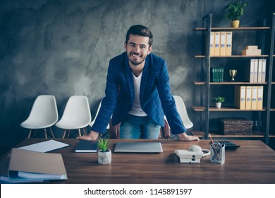 Young business man in blue jacket with beard on face stands at table in office and smiles