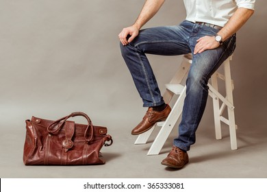 Young business man with a brown leather bag, a white shirt and blue jeans on a gray background