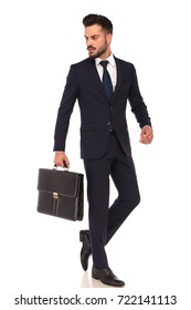 young business man carrying briefcase is walking and looks back over his shoulder on white background