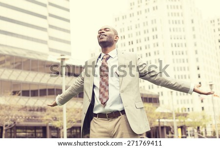 Young business man celebrates freedom success arms raised looking up to sky. Positive human emotions face expression feelings