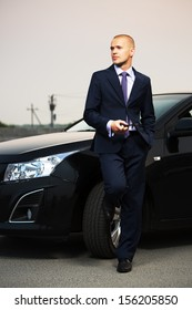 Young business man with a cell phone at the car