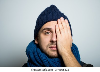 young business man closes one eye, hand, winter style clothes, studio shot isolated on the gray background