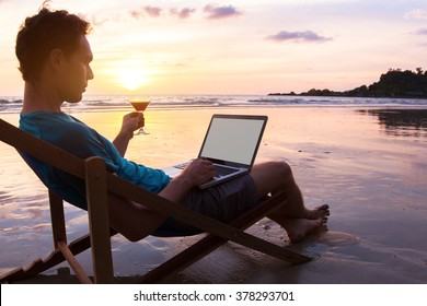 young business man with cocktail working on laptop on the beach at sunset, freelance job online, focus on the screen