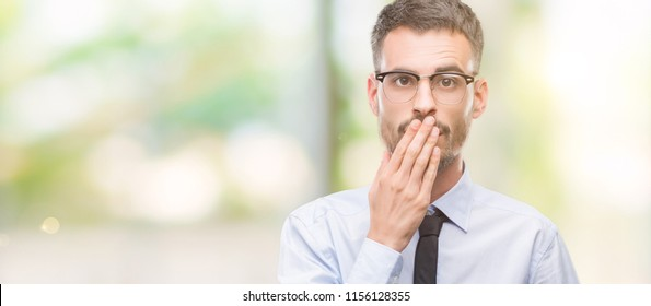 Young business man cover mouth with hand shocked with shame for mistake, expression of fear, scared in silence, secret concept