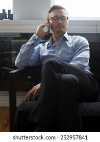 Young business man in dark blue suit pants and in a blue shirt colling with mobile phone in office.