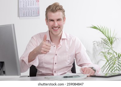 young business man at desk with thumb up
