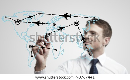 Young business man drawing an airplane routes on world map. Man drawing world map with aircraft flying on a glass window. The metaphor of international air travel around the world