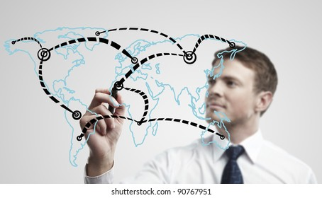 Young business man drawing a global network or globalization concept on world map.  Man drawing internet diagram or business connection on a glass window. On a gray background.