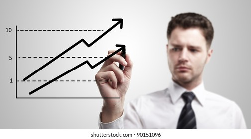 Young business man drawing a graph on a glass window in an office - focus is on graph. Businessman drawing a rising arrow, representing business growth. Man coming up with an idea on a glass screen