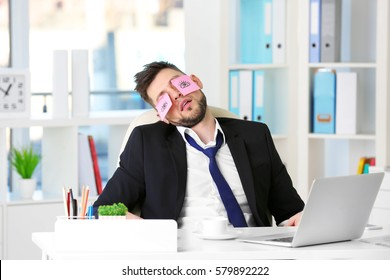 Young business man with fake eyes painted on paper stickers sleeping at workplace in office
