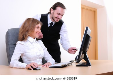 A young business man and a girl running on the computer in the office.