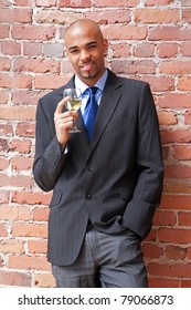 Young business man with a glass of white wine near a brick wall.
