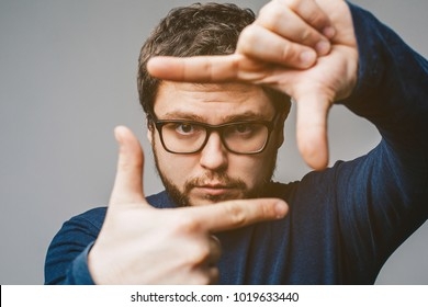Young business man in glasses focusing with fingers, framing with hands isolated on grey background. Close up portrait