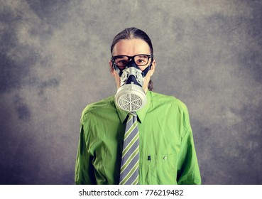 young business man in green shirt with gas mask in front of gray background