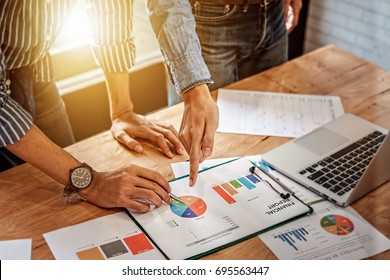 young business man hand holding pen and partner pointing graph chart for  analyze the company's sales plan in the office.