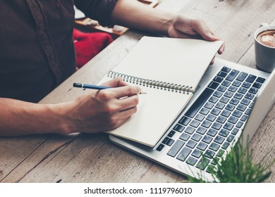 Young business man hand writing notebook and using laptop on wood table.