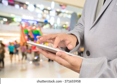 Young Business Man Hands holding Tablet in Shopping Mall or Department Store.