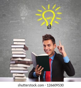 young business man having a great idea while reading an interesting book