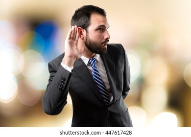 Young business man hearing something over unfocused background
