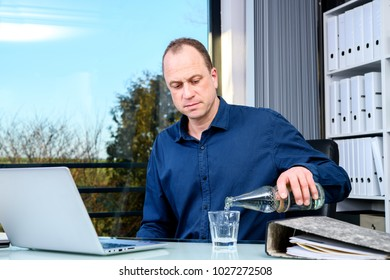 young business man at his desk drinking water