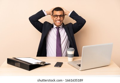 Young business man in his office with a laptop and other documents frustrated and takes hands on head