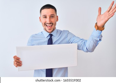 Young business man holding blank banner over isolated background very happy and excited, winner expression celebrating victory screaming with big smile and raised hands