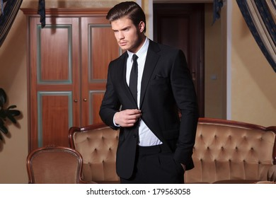 young business man holding a hand in his pocket and one on his jacket's button while looking away from the camera, in a vintage hotel room
