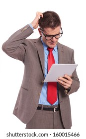 young business man holding his tablet and scratching his head while reading something. on a white background