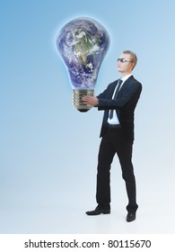 Young business man holding a huge lightbulb