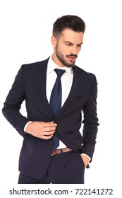 young business man holding suit's button looks down to a side on white background