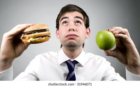 young business man holds apple and burger
