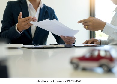 Young Business man insurance agent and customer look at the contract together at the table in office