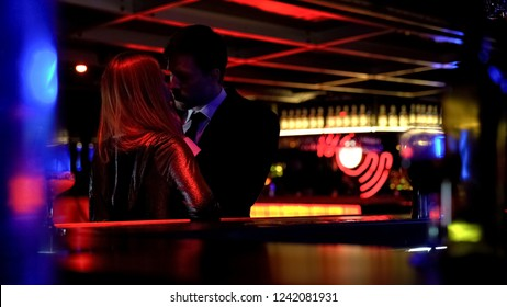 Young business man kissing woman in night club, couple of lovers, temptation