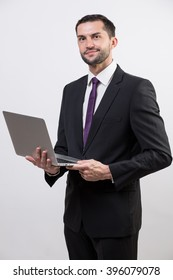 Young business man with a laptop in a studio