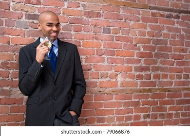 Young business man leaning against the brick wall, drinking wine and smiling.