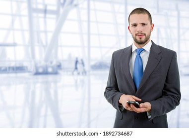 young business man looking to his phone, at the office