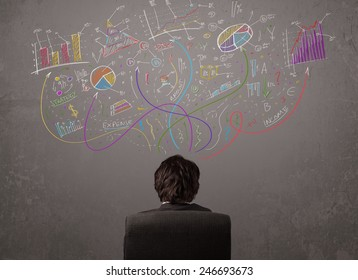 Young business man looking at sketches of graphs and symbols on the wall