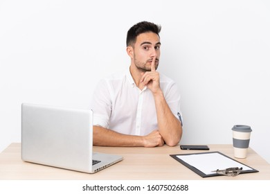 Young business man with a mobile phone in a workplace doing silence gesture