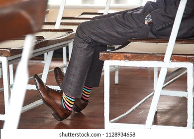 Young business man with nice watch and brown leather shoes and colorful socks on sitting at a ferry with hands in pockets