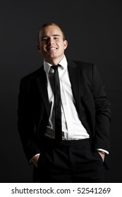 Young business man on black background looking satisfied and smiling