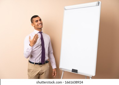 Young business man over isolated background giving a presentation on white board and inviting to come with hand