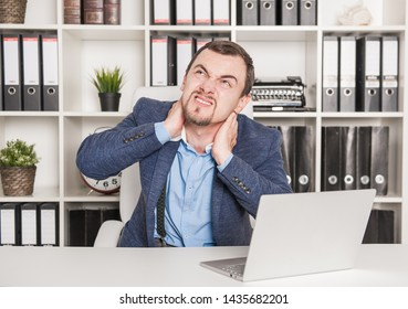 Young business man with pain in neck working in office